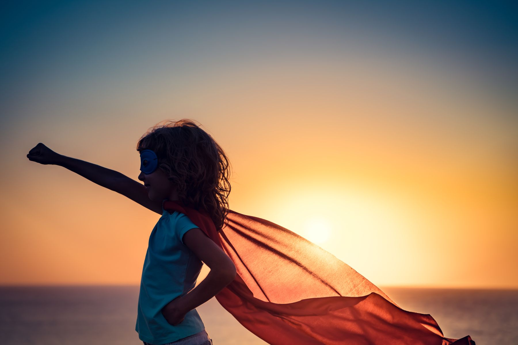 Young girl in a cape with sunset