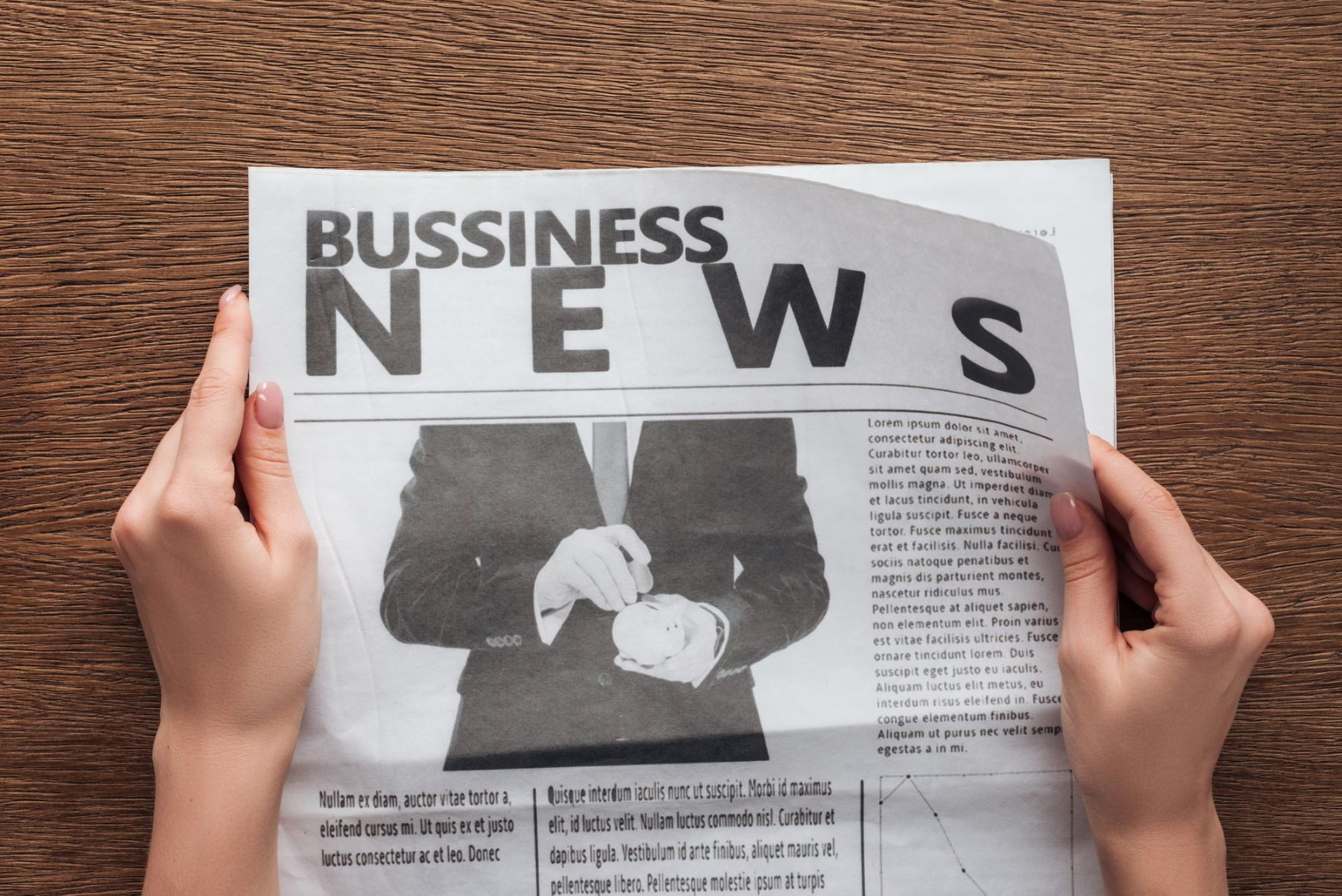 Hands holding business news section of newspaper