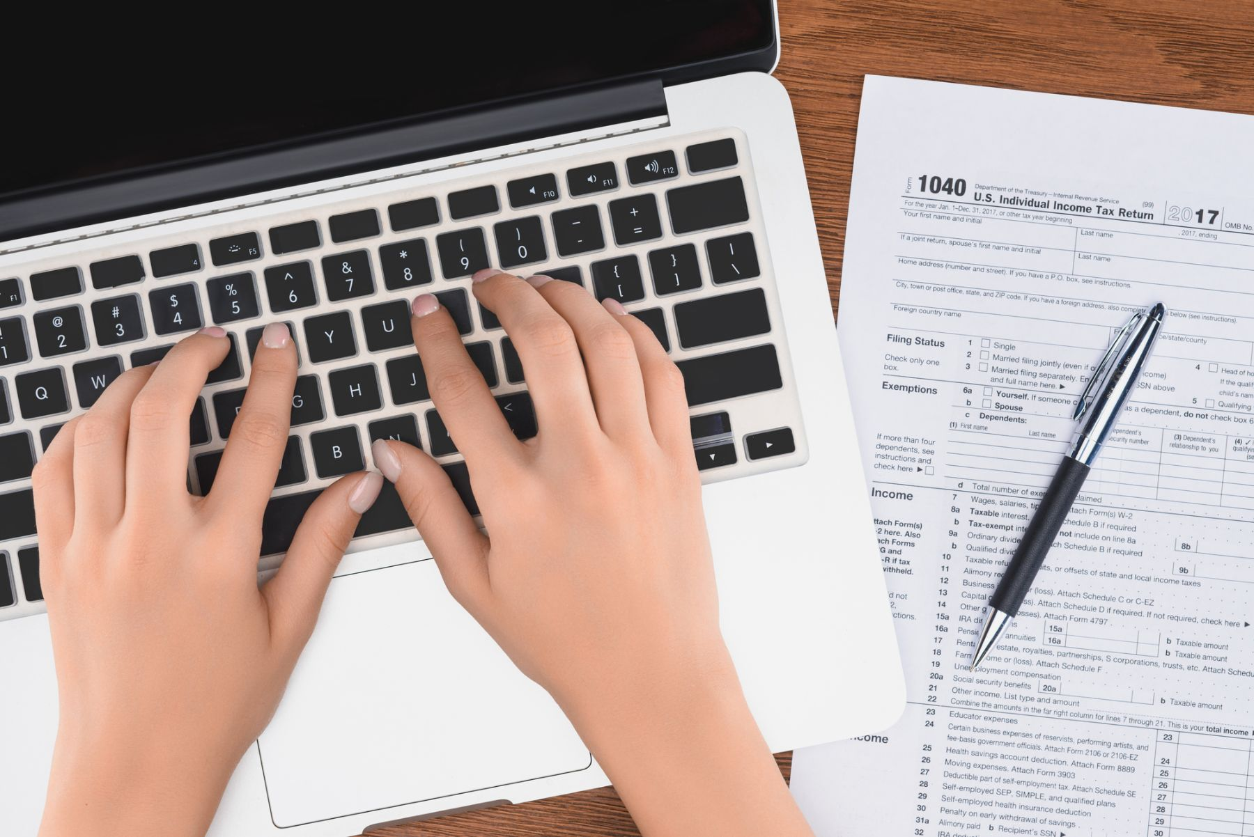 Hands typing on computer with 1040 tax form