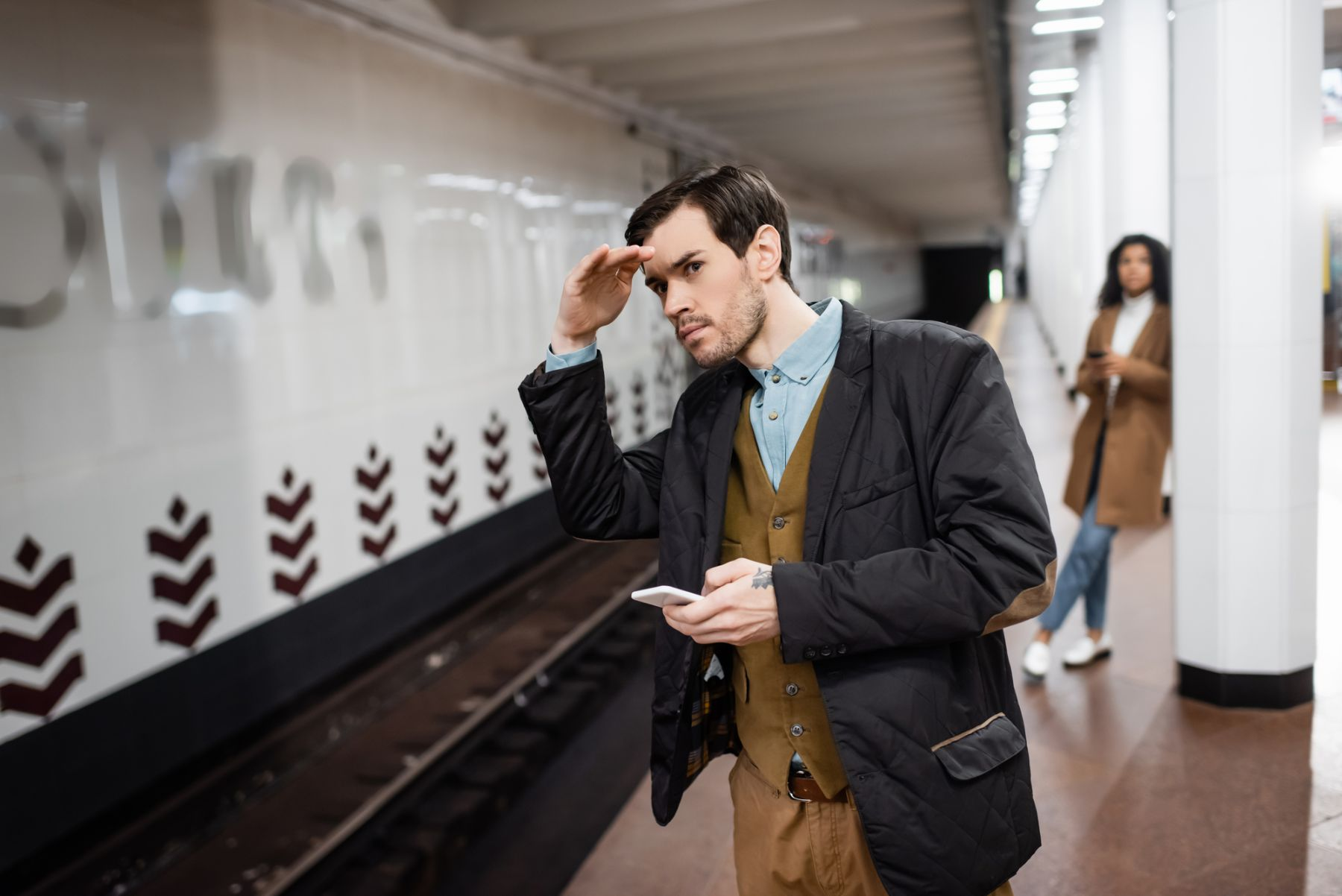 Man holding a phone watching for a train