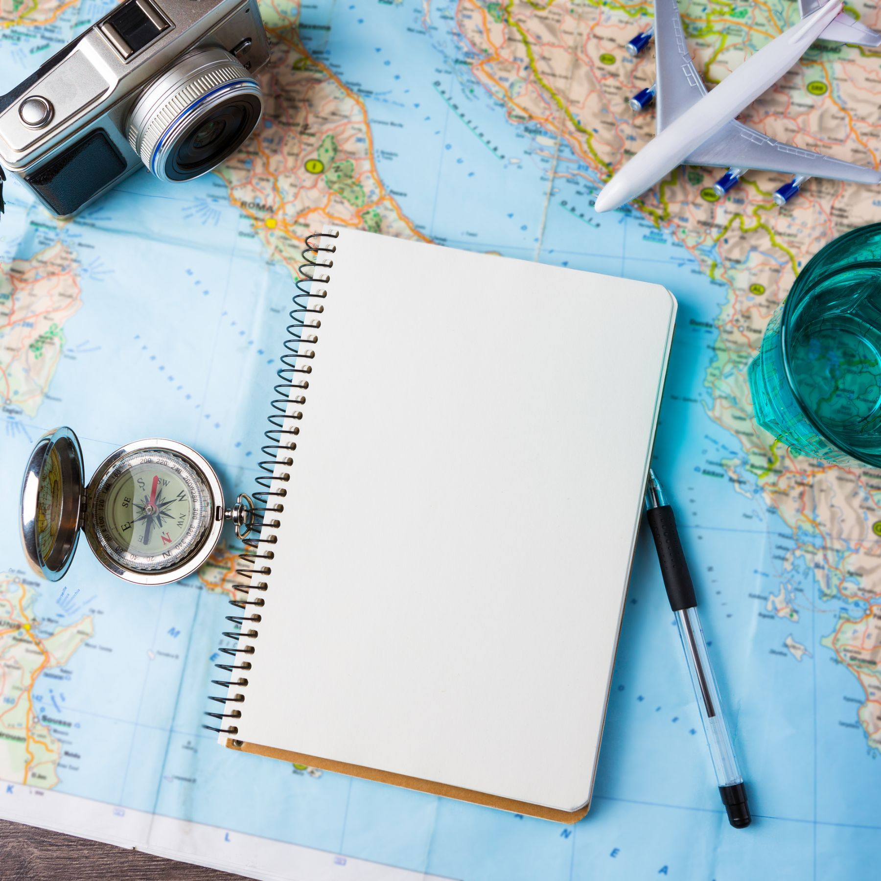 Notebook, camera, plane, pen and a compass on a map