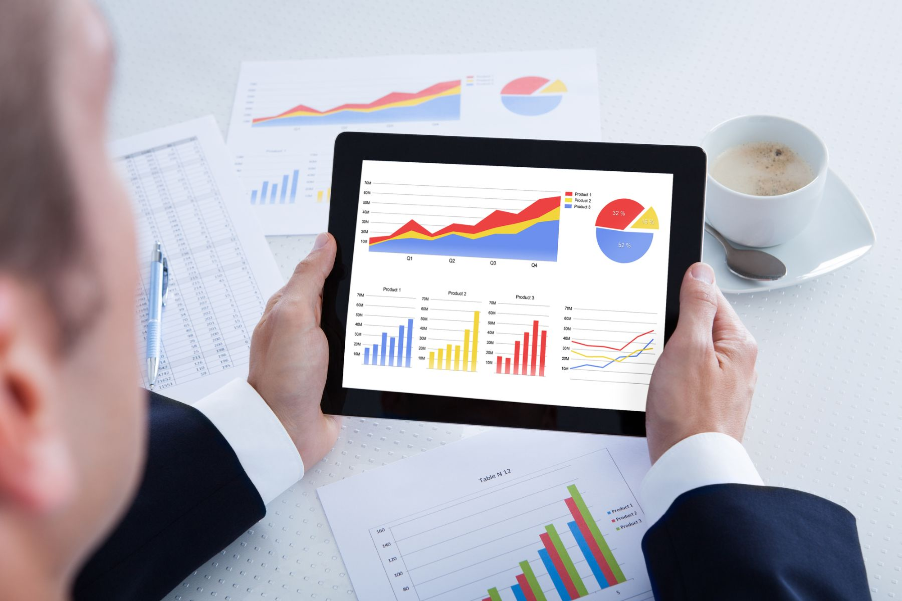 Man looking at data graphs and charts on a tablet and documents