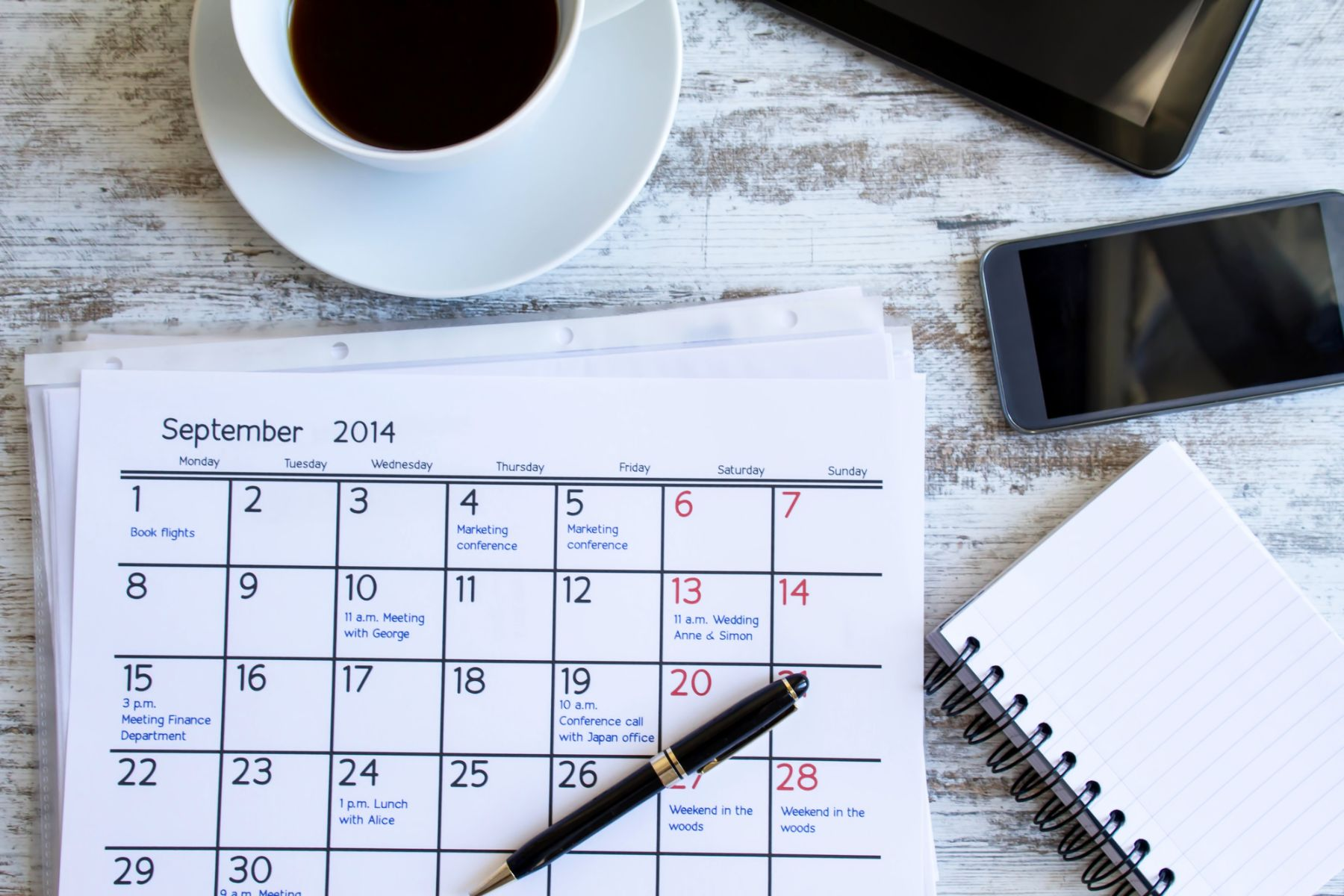 Calendar, pen, notepad and cup of coffee