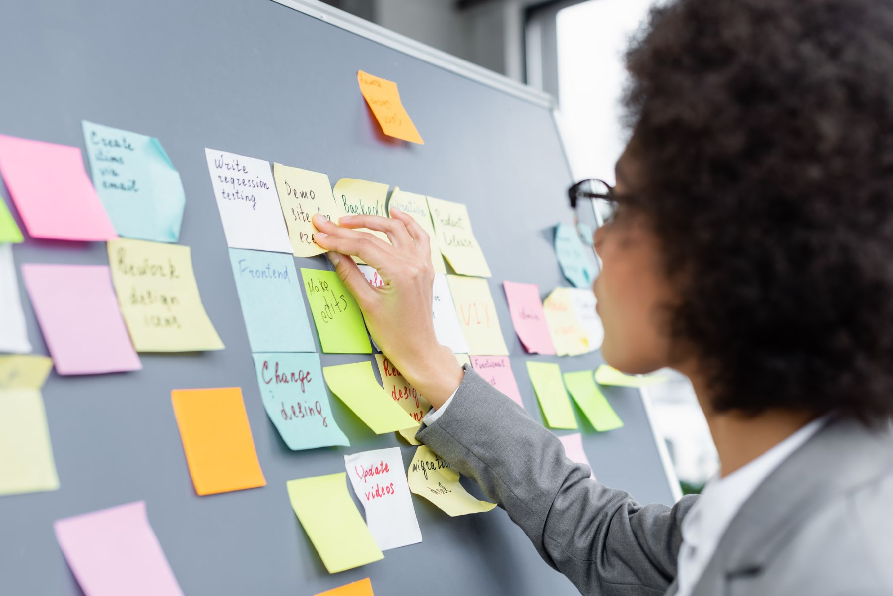 Woman looking at post-it notes on a board
